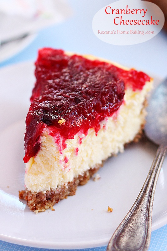 A creamy velvety cheesecake topped with ruby red cranberry sauce. A festive holiday treat perfect for the Thanksgiving or Christmas dessert table. Recipe roxanashomebaking.com