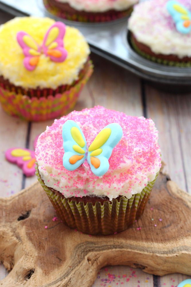 Nutty chocolate cupcakes with a creamy buttercream frosting and decorated with colored sugar, these chocolate almond cupcakes will be a hit with the little ones